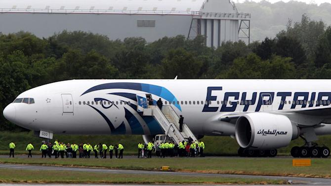 Passengers leave the Egyptair aircraft at  Prestwick Airport, Scotland,   after it was diverted while en route from Cairo to New York, Saturday June 15, 2013.  It is reported that BBC employee Nada Tafik, who was on board the plane, said she found a note in a toilet apparently threatening to start a fire. The plane was escorted to Prestwick by Typhoon fighters from RAF Leuchars, near St. Andrews on the east coast of Scotland.  (AP Photo/ Andrew Milligan /PA)   UNITED KINGDOM OUT