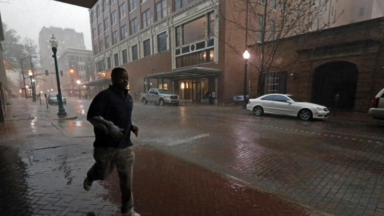 A downtown Jackson, Miss., worker runs along the covered sidewalk to avoid the late afternoon hailstorm, Monday, March 18, 2013. The National Weather Service in Jackson says there were a few super cells in central Mississippi and reports of hail up to baseball size in Clinton. The Mississippi Emergency Management Agency says severe weather has caused damage in at least 10 counties as storms move through parts of the state. (AP Photo/Rogelio V. Solis)