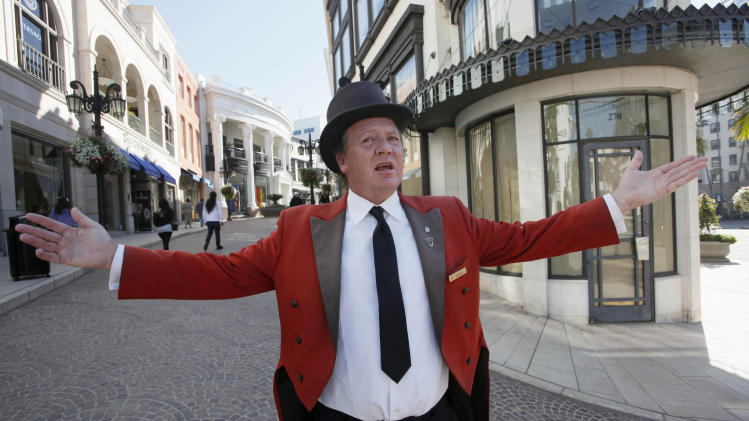 "In this photo taken Feb. 4, 2011, Gregg Donovan, the ambassador of Beverly Hills, Calif., poses on Rodeo Drive in Beverly Hills. Donovan, the jovial, stentorian-voiced actor who has spent much of the past dozen years in top hat and tails giving directions, posing for photos, promoting local businesses and shouting to tourists in dozens of languages, ""Welcome to Beverly Hills, you have arrived!"" is leaving his post on tony Rodeo Drive. Donovan says he was told the Beverly Hills Conference and Visitors Bureau can't afford him anymore. (AP Photo/Nick Ut)"