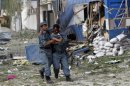 Wounded Afghan policeman is helped away from the site of an explosion in Kabul