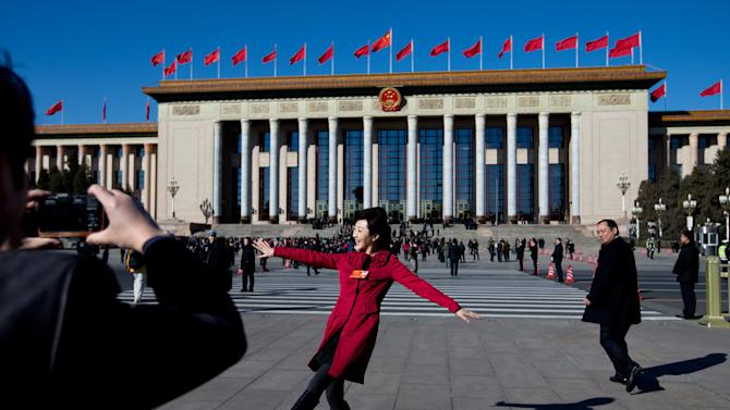A female delegate poses for her colleague taking a souvenir photo in front of the Great Hall of the People as they arrive for sessions of the National People's Congress and the Chinese People's Political Consultative Conference in Beijing Monday, March 4, 2013. The National People's Congress, which opens Tuesday, completes the leadership power transition initiated four months ago, approving top government appointments and giving the new leaders a platform to lay out policies. (AP Photo/Andy Wong)