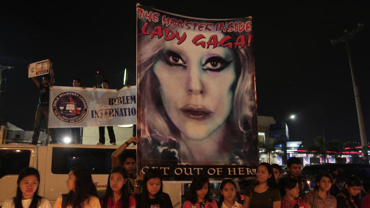"Members of a religious group stand in front of a picture of pop star Lady Gaga as they hold a protest against her concert near the venue in suburban Pasay, south of Manila, Philippines on Monday May 21, 2012. Authorities in the conservative, majority Roman Catholic country approved the concerts, set for tonight, May 21, and Tuesday, but said they won't allow nudity or lewd acts. A religious group warned they will sue Lady Gaga and concert organizers if she sings ""Judas"" during her concert. (AP Photo/Aaron Favila)"