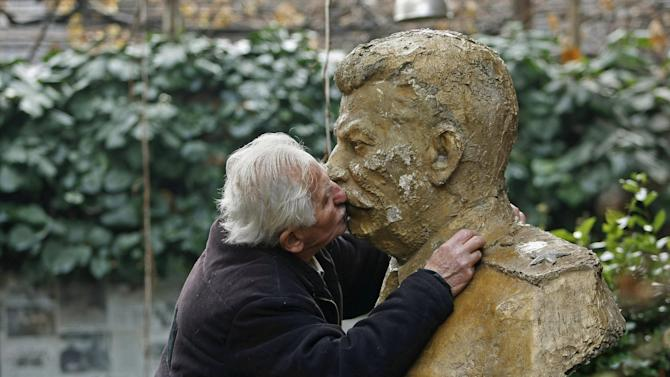 Ushangi Davitashvili kisses the bust of Soviet dictator Josef Stalin that stands in the courtyard of his apartment building in the Georgian capital, Tbilisi, Friday, Dec. 21, 2012. Stalin was born in Georgia in 1879 and led the Soviet Union through decades of totalitarian reforms and political purges. (AP Photo/Shakh Aivazov)