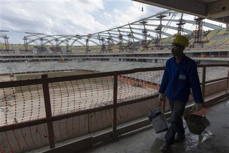 Haitian construction worker Milice Norassaint carries mason's supplies as he walks through the Arena Amazonia soccer stadium in Manaus