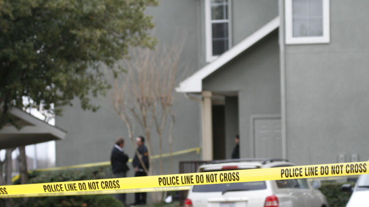 Police tape stretches through a Grapevine, Texas, apartment complex where police found seven people dead in an apartment on Sunday, Dec. 25, 2011 in Grapevine, Texas. Four women and three men who police believe to be related were found apparently shot to death, and authorities said they believe the shooter is among the dead. (AP Photo/Mike Fuentes)