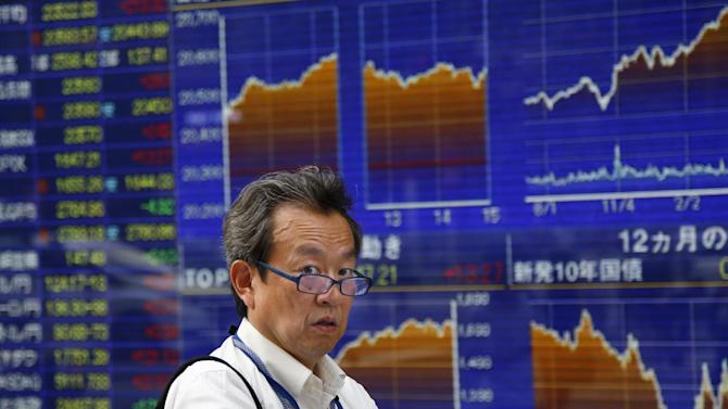 A man walks past an electronic stock indicator of a securities firm in Tokyo, Thursday, July 30, 2015. Chinese stocks fell again Thursday while other major global markets rose after the U.S. Federal Reserve left interest rates unchanged at a record low. Japan's Nikkei 225 advanced 1.1 percent to 20,522.83. (AP Photo/Shizuo Kambayashi)