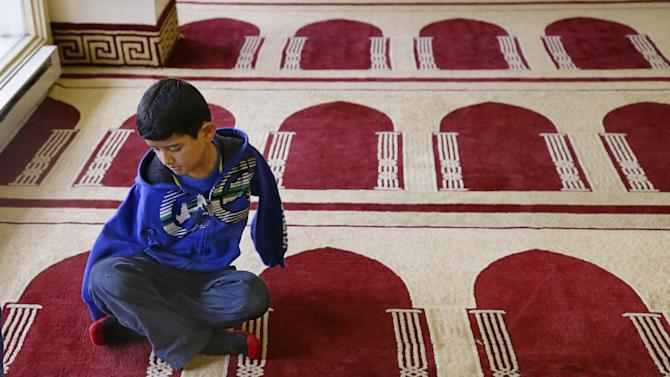 In this Friday, Dec. 18, 2015, photo Syrian refugee Ahmad Alkhalaf, 9, sits on a prayer rug in a mosque in Sharon, Mass. Ahmad, who arrived in the Boston area this past summer for medical treatment, said he used to have restless nights when he would relive his mother's screams from the night a bomb killed three of his siblings and left him without arms. But those sounds, he said, have largely faded. (AP Photo/Stephan Savoia)