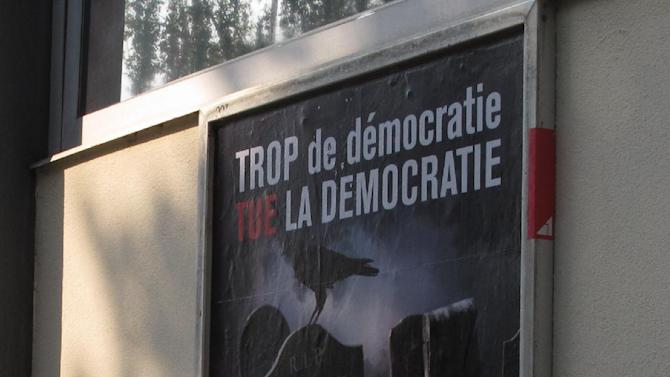FILE - In this picture taken May 24, 2012 a  poster, right, seen in Geneva, Switzerland,  urging Swiss voters to reject a proposal to automatically hold a referendum whenever the government signs an important international treaty. Experts say the proposal by a nationalist group has little chance of passing in a nationwide ballot Sunday but if it did, it would severely curtail the government's power to negotiate treaties .Poster reads . Too much Democracy kills Democracy, and at bottom : No.  (AP Photo/Frank Jordans)