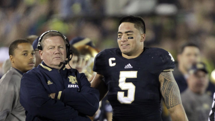 Notre Dame linebacker Manti Te'o, right, pats coach Brian Kelly on the back after Te'o left the game during the second half of an NCAA college football game in South Bend, Ind., Saturday, Nov. 17, 2012. Notre Dame defeated Wake Forest 38-0. (AP Photo/Michael Conroy)
