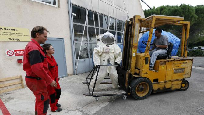 Comex Space division manager Weiss and Comex project engineer Taillebot move the Gandolfi space suit before a training session in Marseille
