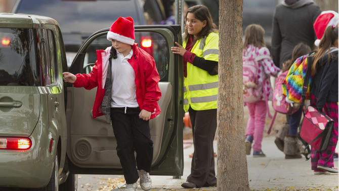 Volunteer parents welcome school children arriving at the Theodore Roosevelt School in Burbank, Calif., early Monday, Dec. 17, 2012. Teachers, parents and students are making an anxious return to school this week after a gunman stormed into Sandy Hook Elementary School in Newtown, Conn., on Friday, shooting to death 26 people before killing himself. (AP Photo/Damian Dovarganes)