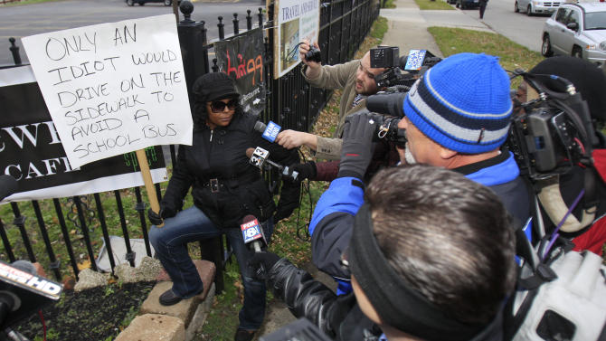 Shena Hardin talks to the media as she holds up a sign while serving a highly public sentence Wednesday, Nov. 14, 2012, in Cleveland.  Hardin drove on a sidewalk to avoid a Cleveland school bus that was unloading children.  Cleveland municipal judge Pinkey S. Carr ordered 32-year-old Hardin to serve the highly public sentence for one hour Tuesday and Wednesday. (AP Photo/Tony Dejak)