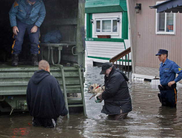 FILE - In this Oct. 30, 2012, file photo, a man walks with his dog to a National Guard vehicle after leaving his flooded home at the Metropolitan Trailer Park in Moonachie, N.J., in the wake of Supers