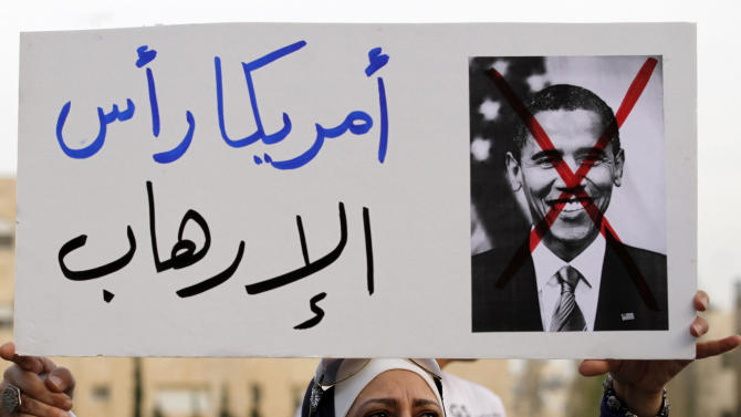 "A Jordanian protester holds a placard depicting U.S. President Barack Obama and in Arabic that reads, ""America is the head of terrorism,"" during a protest near the Israeli embassy against the visit by Obama to the region, in Amman, Jordan, Thursday, March 21, 2013. (AP Photo/Raad Adayleh)"