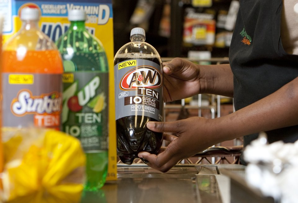 A cashier rings up A&W TEN for a customer shopping at Minyard's Food Store, on Thursday, February, 7, 2013 in Dallas, Texas. Consumers are counting calories more than ever, and beverage companies are responding with new low-calorie options.  In January, Dr Pepper Snapple Group began rolling out ten-calorie versions of five of its most popular soft drink brands including Canada Dry TEN, Sunkist TEN Soda, RC TEN and 7-UP TEN. (Brandon Wade / AP Images for Dr Pepper Snapple Group)