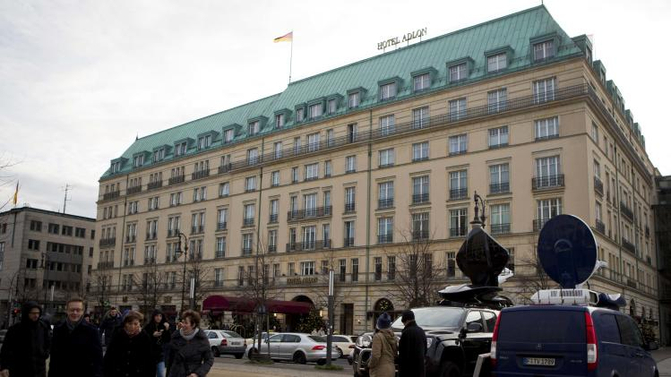Tourists stroll past Adlon Hotel in Berlin