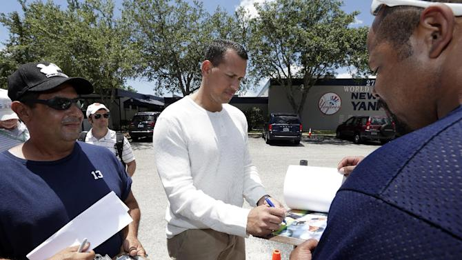 New York Yankees third baseman Alex Rodriguez, center, signs autographs for fans after reporting to the Yankees' Minor League complex for rehabilitation Monday, May 6, 2013, in Tampa, Fla. Rodriguez is rehabbing from hip surgery. (AP Photo/Chris O'Meara)