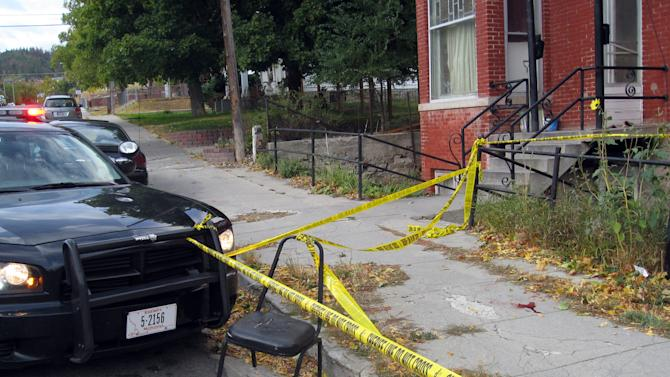 Police tape blocks the road in front of a Helena, Mont., apartment building where a shooting left two dead and one wounded on Thursday Oct. 13, 2011. (AP Photo/Matt Volz)