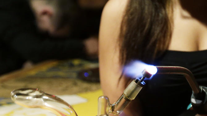 """Jenae DeCampo, a worker in the upstairs lounge area of Stonegate, a pizza-and-rum bar in Tacoma, Wash., uses a blowtorch Saturday, March 2, 2013, to heat the metal part of a bong used to produce marijuana vapor. Bar owner Jeff Call charges patrons a small fee to become a member of the private second-floor club, which prohibits smoking marijuana, but does permit """"vaporizing,"""" a method that involves heating the marijuana without burning it. Last fall, Washington and Colorado became the first states to legalize marijuana use for adults over 21. (AP Photo/Ted S. Warren)"""