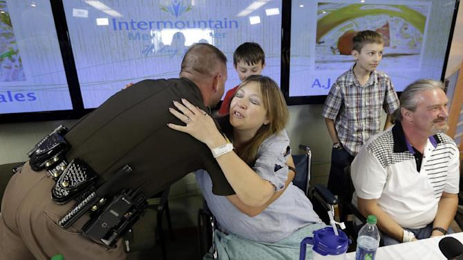 Lynette Hales hugs Utah Trooper Cameron Fawson following a news conference at the Intermountain Medical Center Monday, June 3, 2013, in Murray, Utah. Hales was nearly 100 miles from Salt Lake City on a rural stretch of highway surrounded by nothing but barren salt flats when her twin unborn babies decided it was time. She called police for help, but the nearest highway troopers were about 30 miles east on Interstate 80. The first baby couldn't wait. She delivered him at about 9 a.m. Sunday from the passenger seat of a minivan with the help of a friend who was driving her back from an overnight outing in Wendover. Her twin boys, J.J. and A.J., were born in a minivan with the help of Fawson and her longtime friend Jim Gerber along with two other law enforcement officers. (AP Photo/Rick Bowmer)