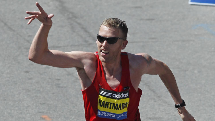 Jason Hartmann, of Boulder, Colo.,  waves as he takes the final strides to the finish line at the 116th Boston Marathon in Boston, Monday, April 16, 2012.  Hartmann finished fourth. (AP Photo/Charles Krupa)