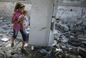 Palestinian girl holding her sister walks through debris near remains of a mosque, which witnesses said was hit by an Israeli air strike, in Beit Hanoun in the northern Gaza Strip