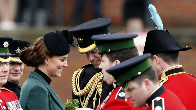 Britain's Kate Duchess of Cambridge, third left, stands with her husband Prince William, fourth left, before presenting traditional sprigs of shamrock to members of the 1st Battalion Irish Guards at the St Patrick's Day Parade at Mons Barracks in Aldershot, England, Sunday, March 17, 2013.  Kate presenting the sprigs of shamrocks to the regiment Sunday, follows a century-old tradition inaugurated by Queen Alexandra, the wife of the then King, Edward VII back in 1901.  (AP Photo/Matt Dunham)