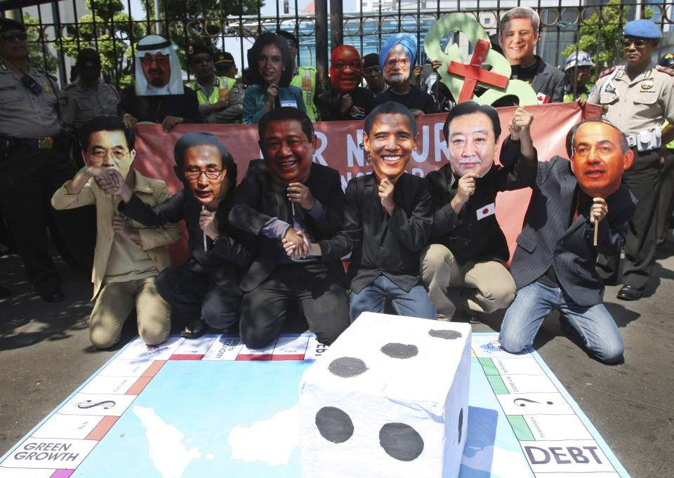 Protesters enact leaders of countries attending the Group of 20 summit meeting playing monopoly during a rally in Jakarta, Indonesia, Tuesday, June 19, 2012. The demonstrators criticized the economic policies implemented by the G20 leaders. (AP Photo/Achmad Ibrahim)