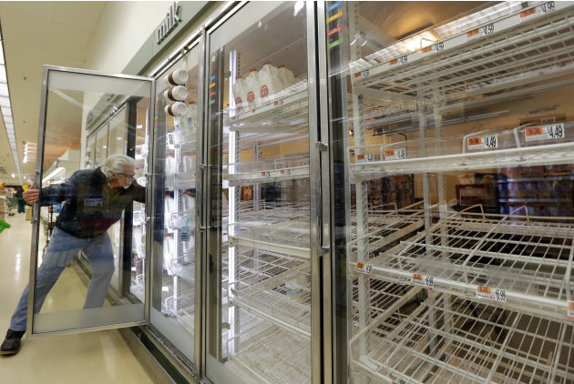 Jack Percoco of Cambridge, Mass. reaches into depleted shelves for milk at a supermarket in Somerville, Mass., Friday, Feb. 8, 2013. A major winter storm is heading toward the U.S. Northeast with up t