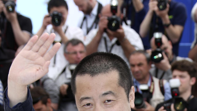 Director Jia Zhangke waves at photographers during a photo call for the film Stranger by the Lake at the 66th international film festival, in Cannes, southern France, Friday, May 17, 2013. (Photo by Joel Ryan/Invision/AP)