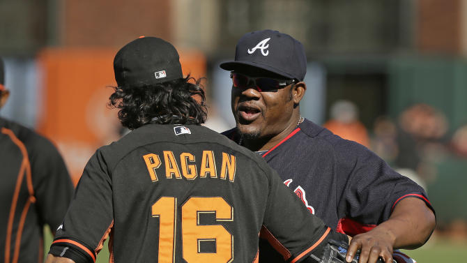 San Francisco Giants center fielder Angel Pagan, left, greets Atlanta Braves third baseman Juan Uribe, right, before the start of their baseball game Thursday, May 28, 2015, in San Francisco. Uribe, who played for the Giants in 2009 and 2010, was traded from the Los Angeles Dodgers to the Braves earlier in the week. (AP Photo/Eric Risberg)