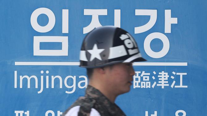 A South Korean army soldier walks by a signboard showing the distance to North Korean capital Pyongyang and that for South's capital Seoul from Imjingang Station near the border village of Panmunjom in Paju, South Korea, Thursday, Feb. 14, 2013. North Korea's neighbors bolstered their military preparations and mobilized scientists Wednesday to determine whether Pyongyang's third nuclear test, conducted in defiance of U.N. warnings, was as successful as the North claimed.(AP Photo/Ahn Young-joon)