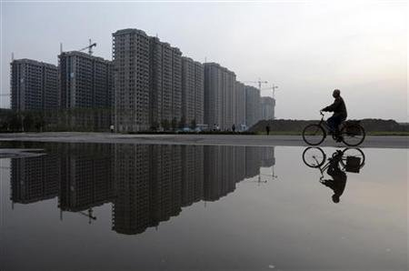 Man cycles past a residential complex under construction, which is reflected in a puddle, in Taiyuan