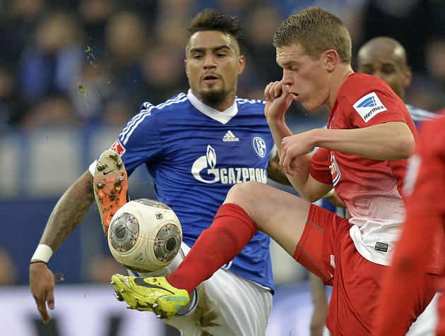 Schalke's Kevin-Prince Boateng, left, and Freiburg's Matthias Ginter challenge for the ball during the German Bundesliga soccer match between FC Schalke 04 and SC Freiburg in Gelsenkirchen, Ge