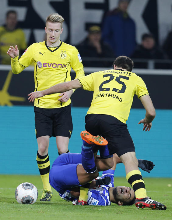 Dortmund's Marco Reus, left, Dortmund's Sokratis of Greece, right, and Berlin's Sami Allagui of Tunesia challenge for the ball during the German first division Bundesliga soccer match betw