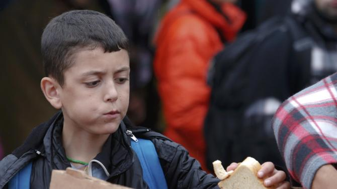 A  boy grabs a piece of bread as he arrives at the Austrian train station of Nickelsdorf to board a train to Germany