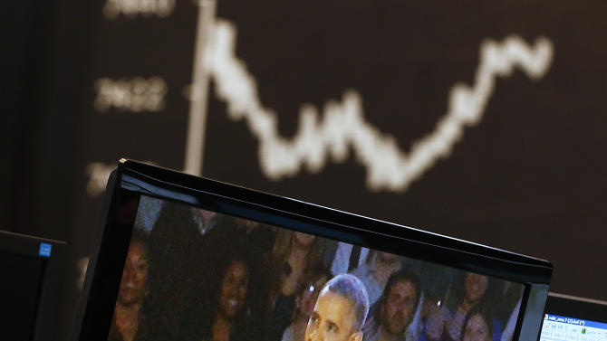 The curve of the German stock index DAX is pictured as news about the US elections appear on e television screen at the stock market in Frankfurt, Germany, Wednesday, Nov. 7, 2012. (AP Photo/Michael Probst)
