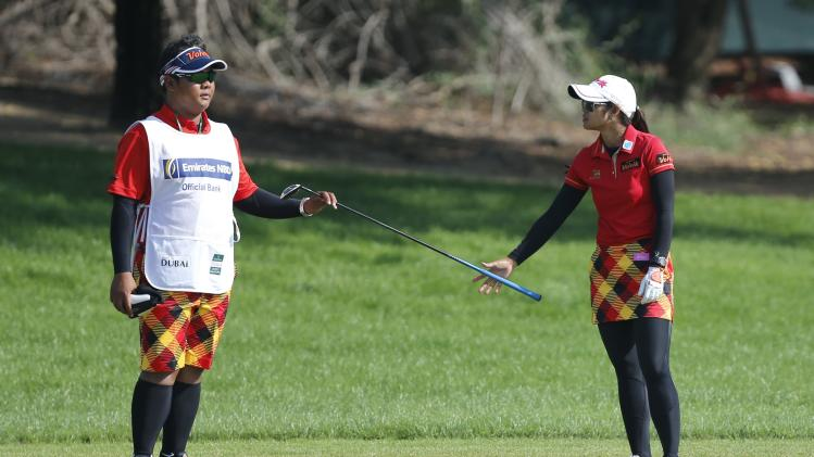 Pornanong Phatlum of Thailand hands over the club to her caddy on the ninth hole during Dubai Ladies Masters golf tournament in Dubai