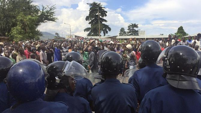 Burundian riot police and opposition demonstrators confront each other in the capital Bujumbura, Burundi Monday, April 27, 2015. Street protests continued Monday in Burundi as anger mounts over the ruling party's decision on Saturday to nominate President Pierre Nkurunziza for a third term. (AP Photo/Andrew Njuguna)