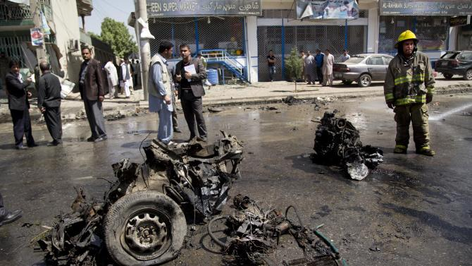 An Afghan fireman stands next to the debris of a car at the scene where a suicide car bomber attacked a NATO convoy in Kabul, Afghanistan, Thursday, May 16, 2013. A Muslim militant group, Hizb-e-Islami, claimed responsibility for the early morning attack, killing many in the explosion and wounding tens, police and hospital officials said. The powerful explosion rattled buildings on the other side of Kabul and sent a pillar of white smoke into the sky in the city's east. (AP Photo/Anja Niedringhaus)