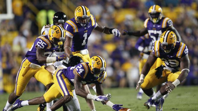 LSU cornerback Tharold Simon (24) reaches for a Towson fumble as Kwon Alexander (25), Eric Reid (1), Sam Montgomery (99) and Lamin Barrow (57) join the chase in the first half of an NCAA college football game in Baton Rouge, La., Saturday, Sept. 29, 2012. Simon recovered the fumble. (AP Photo/Bill Haber)