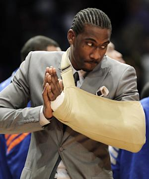In this Thursday, May 3, 2012, photo, New York Knicks forward Amare Stoudemire watches from the baseline with his arm in a sling before Game 3 of an NBA basketball first-round playoff series at Madison Square Garden in New York. Stoudemire sat the game out after a surgeon repaired a muscle in his hand Tuesday after he cut it punching through the glass of a fire extinguisher case following Game 2. Stoudemire played in Game 4 of the series on Sunday, scoring 20 points. (AP Photo/Kathy Willens)