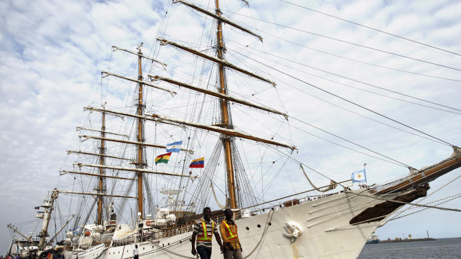 FILE - In this Oct. 23, 2012 file photo, port workers walk past the three-masted ARA Libertad, a symbol of Argentina's navy, as it lies docked at the port in Tema, outside Accra, Ghana. Sailors aboard the navy sailing ship seized in a billion-dollar international debt controversy brandished weapons to block Ghanaian officials from moving the vessel to a less busy dock, an official of the Ghana Ports and Harbors Authority said Saturday, Nov. 10, 2012. (AP Photo/Gabriela Barnuevo, File)