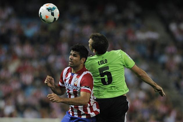 Atletico de Madrid's Diego Costa from Brazil, left, in action with Osasuna's Lolo, right, during a Spanish La Liga soccer match at the Vicente Calderon stadium in Madrid, Spain, Tuesday, Sept. 24, 201