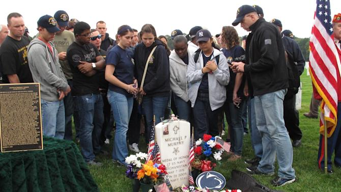 Crew members from the USS Michael Murphy gather at the gravesite of the Navy SEAL during a memorial service at Calverton National Cemetery in Calverton, N.Y. on Tuesday, Oct. 2, 2012. USS Michael Murphy, a Navy destroyer named for the Medal of Honor recipient killed in Afghanistan in 2005, will be commissioned in New York City on Saturday, Oct. 6, 2012. (AP Photo/Frank Eltman)