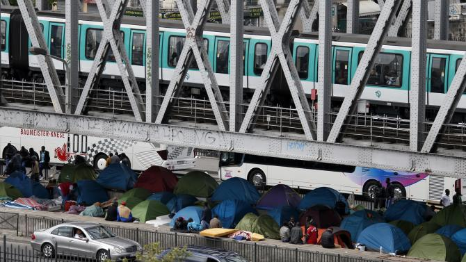 An elevated metro passes over a bridge where migrants have established a make-shift tent city in Paris