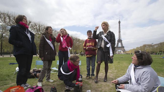 Frigide Barjot, leader of the movement against gay marriage, 2nd right, talks to the media as she visits mothers, who take part in a vigil to protest against French President Francois Hollande's social reform on gay marriage and adoption next to the Eiffel tower in Paris, Monday, April 22, 2013. Both houses of the French parliament have already approved the bill in a first reading. The second and final reading is expected Tuesday. Eiffel tower is seen in the background. (AP Photo/Michel Euler)