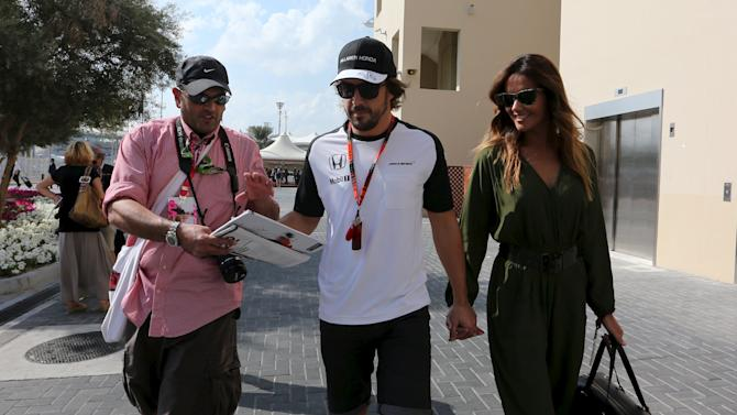 McLaren Formula One driver Fernando Alonso of Spain signs an autograph for a fan as he arrives with his girlfriend Lara Alvarez ahead of the Abu Dhabi F1 Grand Prix at the Yas Marina circuit in Abu Dhabi