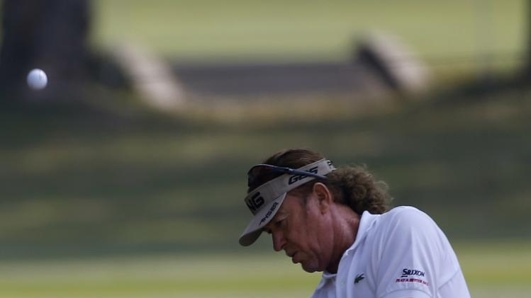 Defending champion Miguel Angel Jimenez from Spain chips a shot onto the ninth green during the second day of the European Tour Hong Kong Open golf tournament