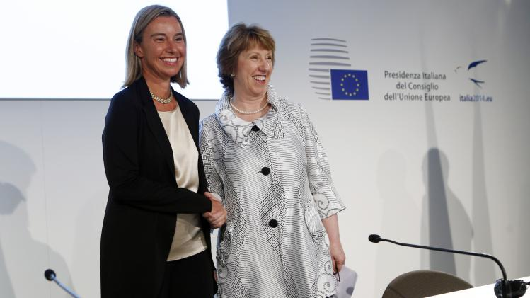 Mogherini shakes hand with Ashton before a news conference at the end of an informal meeting of the EU Foreign Affairs Ministers in Milan